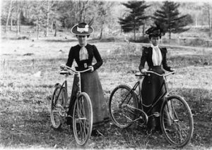 Two women riding bicycles in long skirts, circa 1900. Photo Courtesy of The Larry Hart Collection